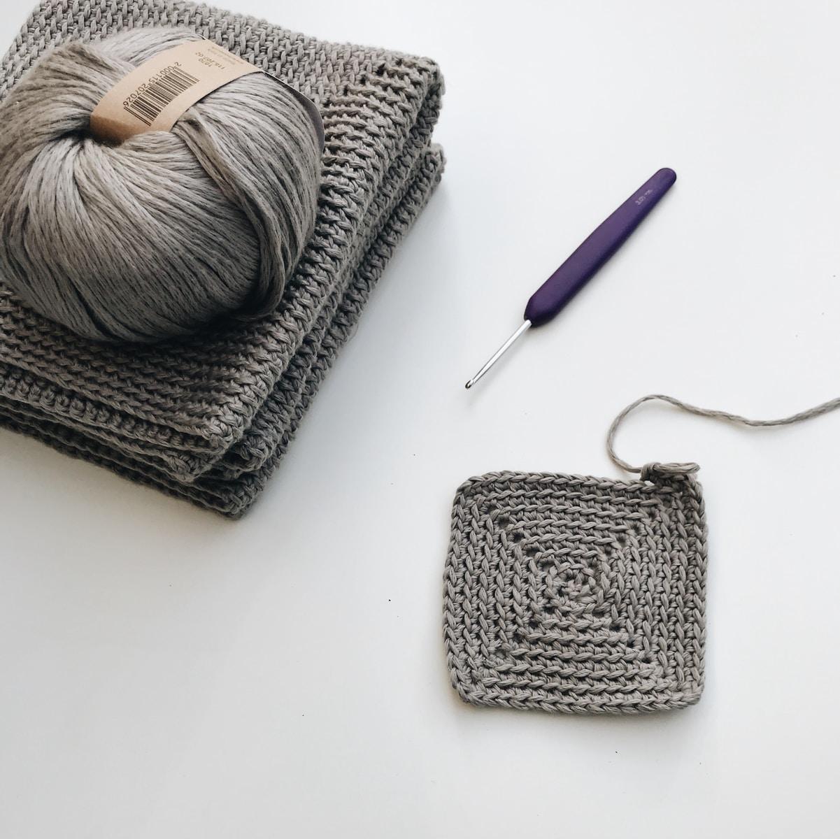 blue pen beside gray yarn
