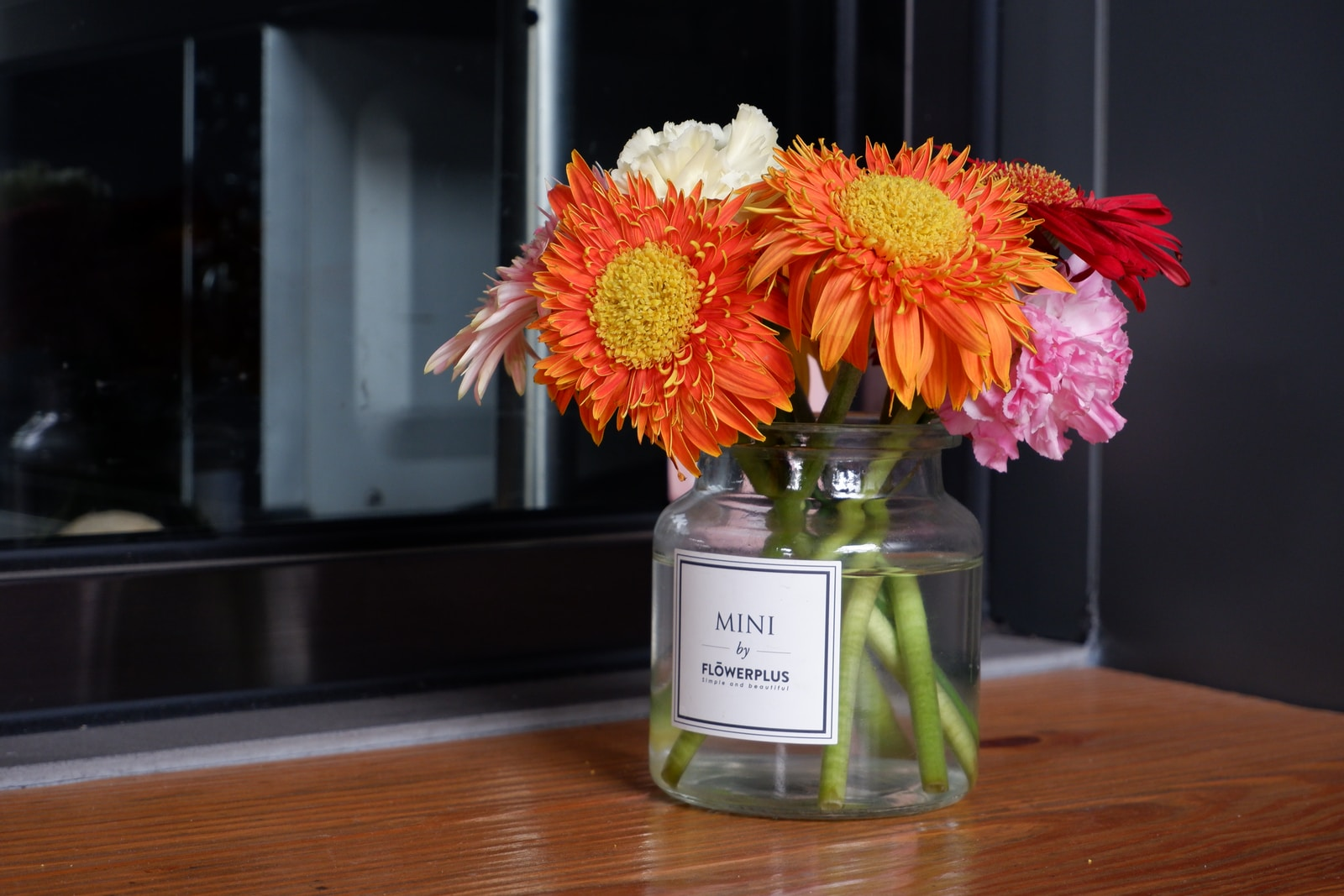 yellow and red flowers in glass bottle